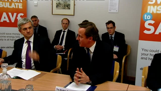 energy companies agree measures to help reduce household bills england london int david cameron mp and chris huhne mp sitting at roundtable energy... - クリス ヒューン点の映像素材/bロール