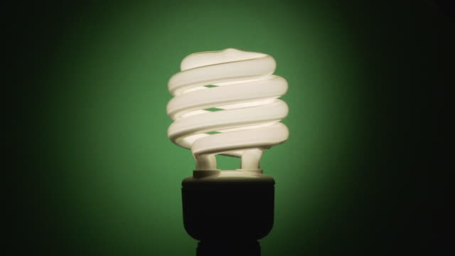 ms, energy efficient light bulb revolving against green background - energy efficient lightbulb stock videos and b-roll footage