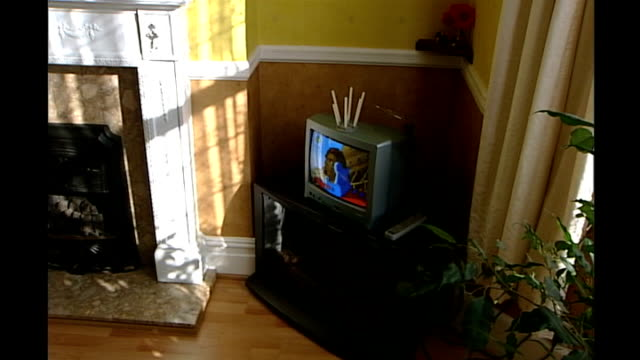 vídeos de stock, filmes e b-roll de electricity companies plan to install 'smart meters' in customers homes; television on in a living room, family members eating - smart