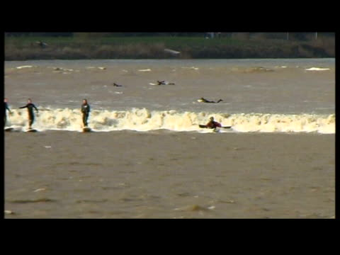 stockvideo's en b-roll-footage met government expected to back nuclear power in future energy plans; lib 30.3.2002 england: river severn: ext surfers along on severn bore wave - itv weekend evening news
