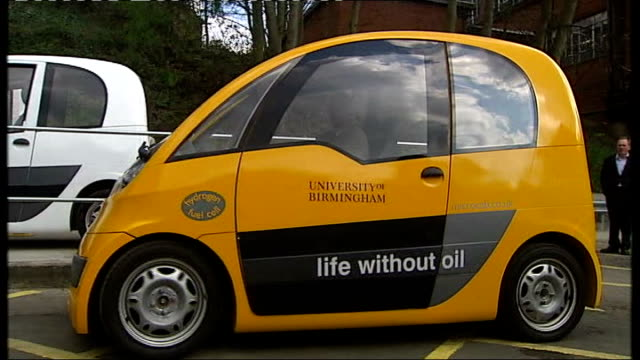 vídeos de stock, filmes e b-roll de uk's first hydrogen fuel station opens in birmingham yellow microcab with 'life without oil' slogan on side along on garage forecourt / various of... - hidrogênio