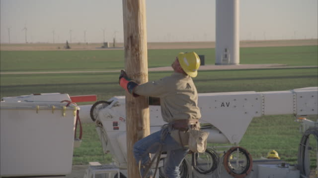cu zo aerial energy worker climbing on power pole, farms in background / hooker, ok, usa - energia rinnovabile video stock e b–roll
