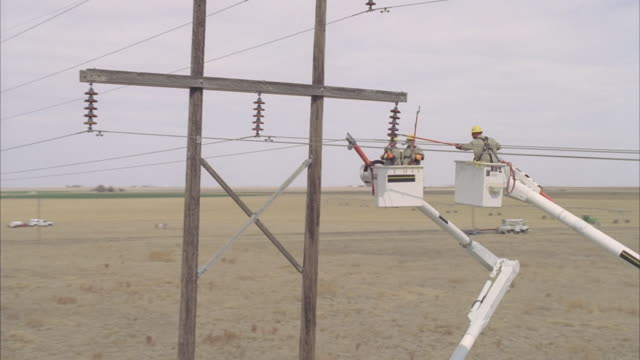 ws aerial energy workers adjusting copper coil connected to powerline from safety of two cherry pickers / hooker, ok, usa - 発電所関係の職業点の映像素材/bロール