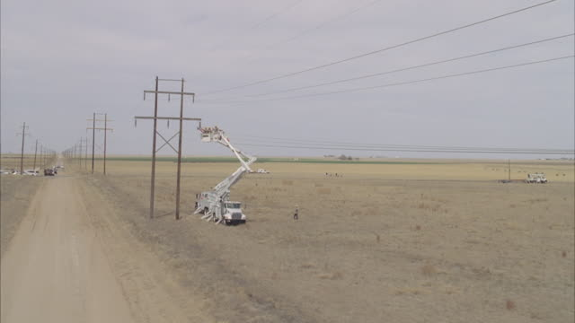 ws ts aerial energy workers adjusting powerline above dirt road surounded by fields / hooker, ok, usa - adjusting stock videos & royalty-free footage