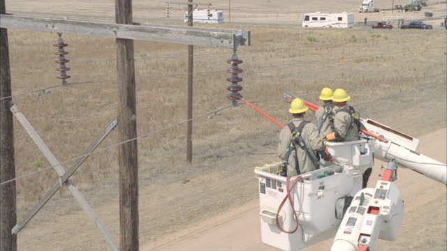 MS ZI AERIAL Energy workers adjusting powerline with long red tools / Hooker, OK, USA