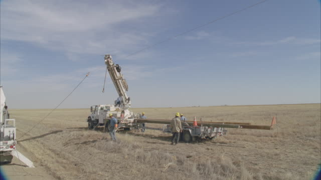 ws aerial pan energy workers planting power line pole into ground / hooker, ok, usa - telegraph pole stock videos and b-roll footage