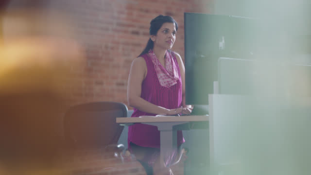 engaged employee working quickly and confidently at her standing desk - small office stock videos & royalty-free footage