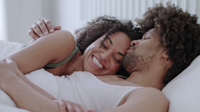 engaged mid adult happy dark-skinned love couple caressing together at home in white bed on a day-off morning while enjoying themselves. - 小背心 個影片檔及 b 捲影像