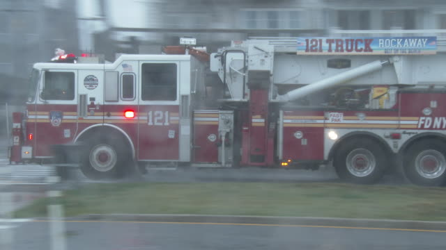 engine 265 ladder 121 runs it's lights and sirens as it heads west down shore front parkway during tropical storm fay in rockaway queens new york new... - scott mcpartland stock videos & royalty-free footage