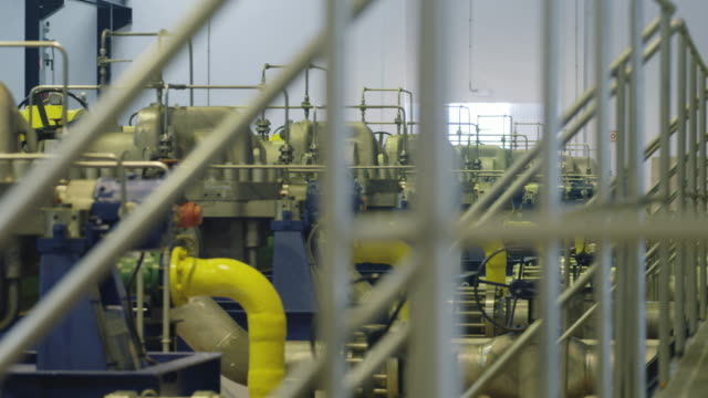 PAN LS engine and compressor hall of water treatment plant, PAN ends on worker on gangway holding clipboard, RED R3D 4K