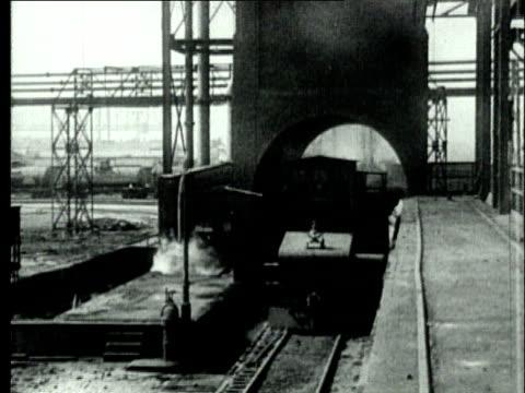 1927 B/W WS TU TD Engine travelling on rail tracks beneath tower in coke production yard/ Pennsylvania, USA