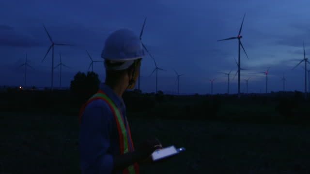 engineer a wind turbine evaluation at night - attrezzatura industriale video stock e b–roll
