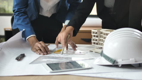 engineer and architect active discussion of plans on blueprint, business working - work helmet stock videos & royalty-free footage