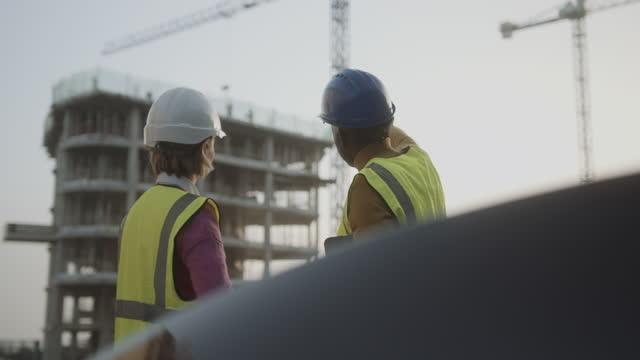 vidéos et rushes de engineer and architect team meeting on building construction site discussing progress - classe ouvrière