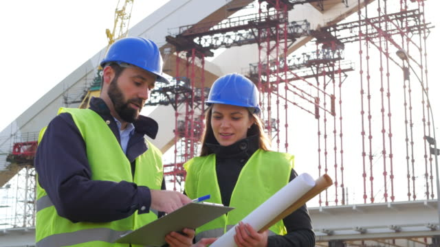 Engineer and architect with blueprints on construction site