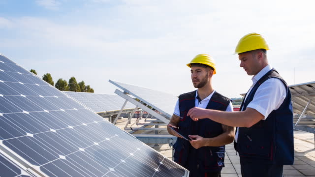 cu engineer and construction worker examining solar panels on rooftop - bauarbeiter stock-videos und b-roll-filmmaterial