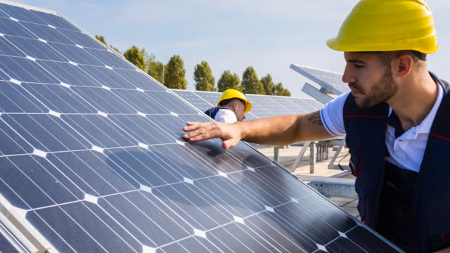 cu engineer and construction worker examining solar panels on rooftop - roof stock videos & royalty-free footage
