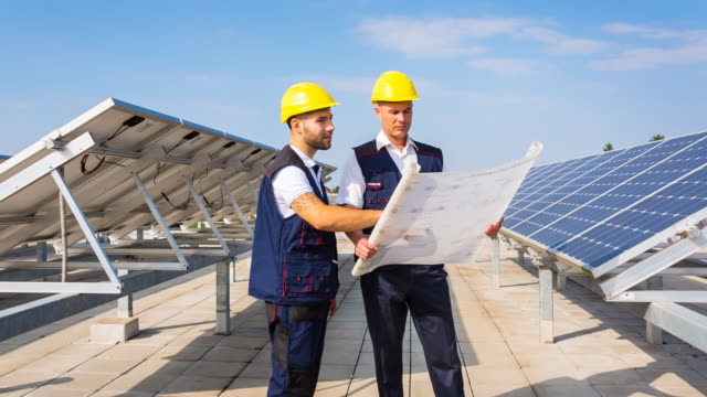 MS engineer and construction worker examining solar panels on rooftop