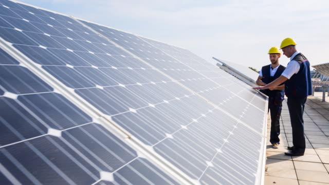 vídeos y material grabado en eventos de stock de ms engineer and construction worker examining solar panels on rooftop - energía solar