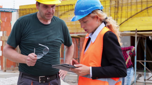 engineer and construction worker talking. - construction site stock videos and b-roll footage