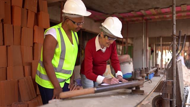 建設現場での文書の分析と署名を行うエンジニアと請負業者 - 土木技師点の映像素材/bロール