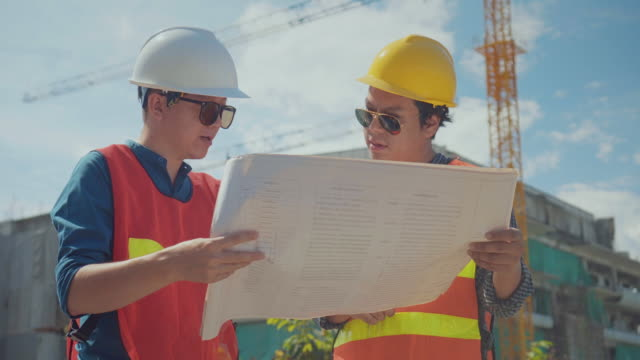 engineer and foreman with blueprints talking at construction site,dolly shot - caposquadra video stock e b–roll