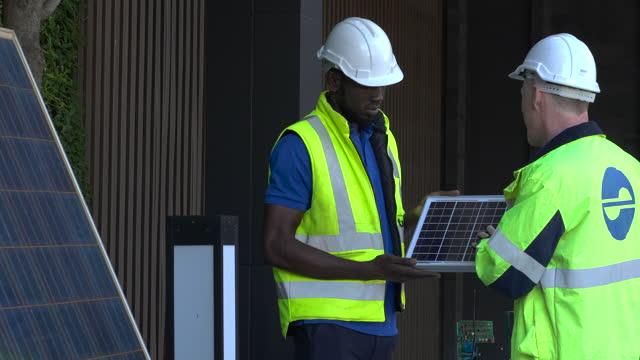 ingegnere e tecnico che discutono per controllare l'energia di sostituzione delle celle solari - elmetto da cantiere video stock e b–roll