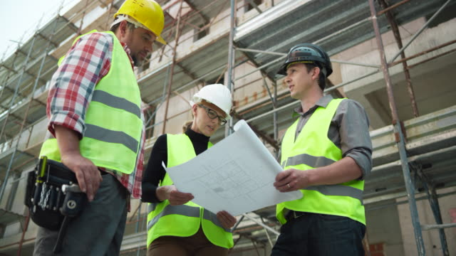 engineer, architect and foreman talking and holding the plans at the construction site - sleeve stock videos & royalty-free footage