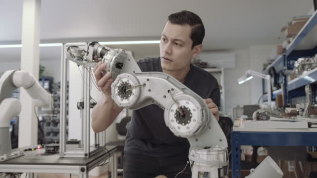 engineer building a robotic arm - maschinelles lernen stock-videos und b-roll-filmmaterial