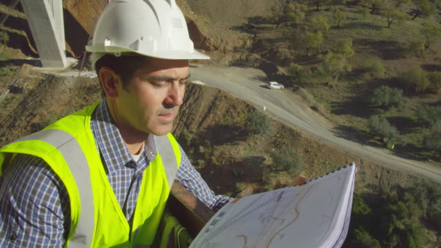 engineer checking plans standing in man rider suspended from crane in freeway bridge construction site