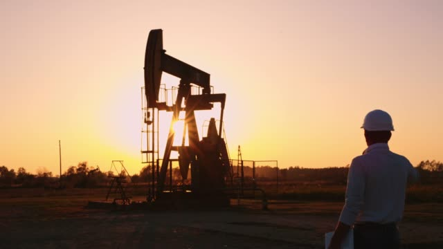 DS Engineer checking the oil well at sunset