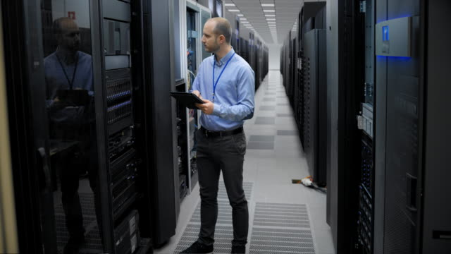 it engineer checking the servers in the server room with a help of a tablet - it professional stock videos & royalty-free footage