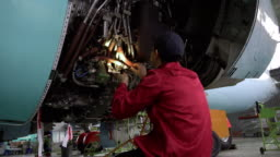 Engineer checks the engine of the aircraft. The repair of aircraft in the hangar
