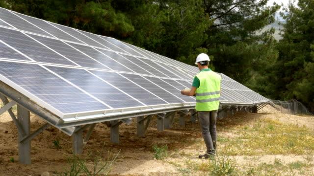 ingenjör kontrollerar solpanelerna i fältet, miljövänlig elproduktion, hållbar förnybar energi - ansvarsfullt företagande bildbanksvideor och videomaterial från bakom kulisserna