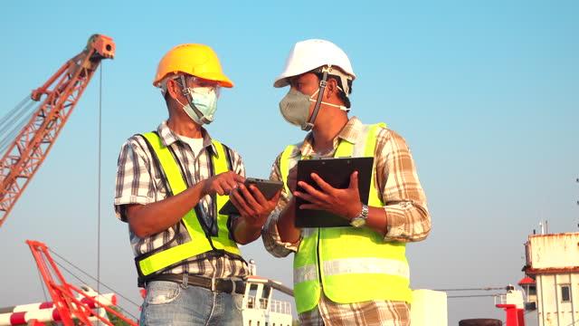 建設現場の同僚や、建設または海運産業の造船所のバックグラウンドでエンジニアとのディスカッション。 - 造船所点の映像素材/bロール