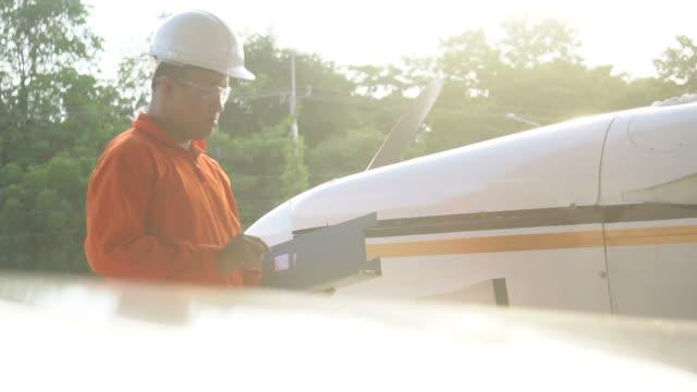 ingenieur prüfung flugzeug im laderaum bei sonnenuntergang - techniker stock-videos und b-roll-filmmaterial