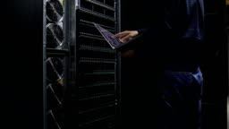 Engineer examining with topological graph in Server room