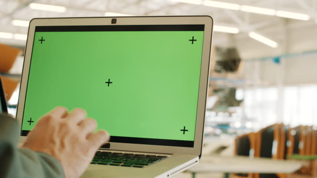 Ingeniero con laptop con clave de pantalla verde chroma