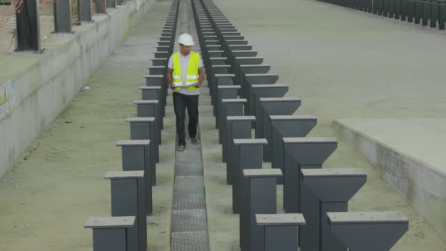 LS TD engineer holding plan walking through rows of steel columns towards camera, RED R3D 4K