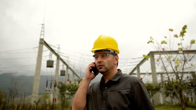 vídeos de stock e filmes b-roll de engenheiro na estação de alimentação frente a usar um telefone - engenheiro de manutenção
