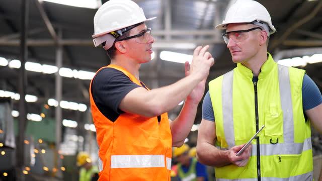engineer in hard hat and factory worker talking - metal worker stock videos & royalty-free footage