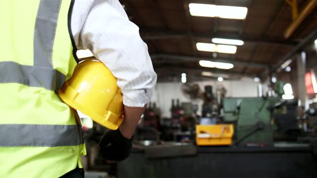 ingegnere in hardhat camminando in fabbrica - elmetto da cantiere video stock e b–roll
