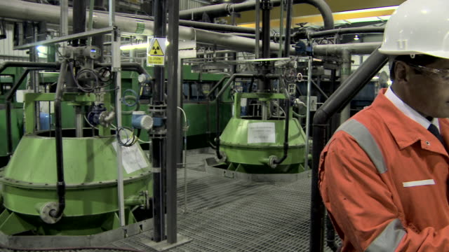 engineer inspecting machinery in factory - helm stock-videos und b-roll-filmmaterial