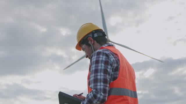 ingenjör inspekterar vindkraftverk - planering bildbanksvideor och videomaterial från bakom kulisserna