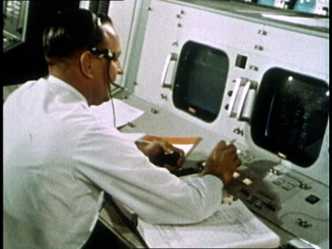 NASA engineer making report at control room console / United States