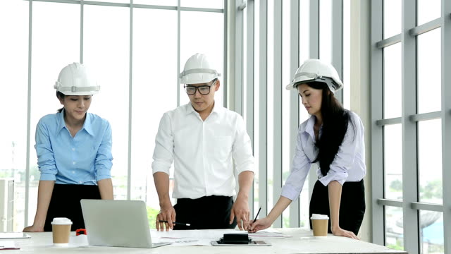 engineer man and women discussing blueprint building project plan on the table at construction site - helmet stock videos & royalty-free footage