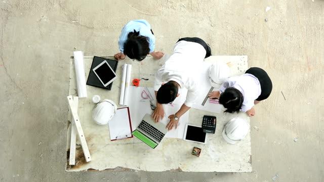 vidéos et rushes de ingénieur homme et femmes discutant plan plan de projet de construction de comparer avec les données sur ordinateur portable écran vert sur la table au chantier de construction - keyable