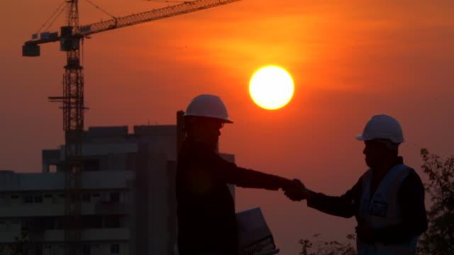 Ingenieur van beheer met groep van ingenieurs vergadering op bouwplaats