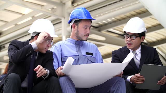 vídeos y material grabado en eventos de stock de ingeniero del proyecto proyecto sostiene y explica detalles del proyecto con la administración mientras busca en el sitio de construcción. - asia sudoriental