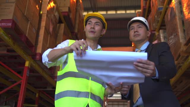 プロジェクトのエンジニアは、工場倉庫を見ながら、設計図を保持し、経営陣とプロジェクトの詳細について話し合います。 - 設計図点の映像素材/bロール